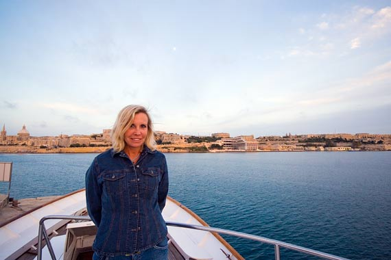 Karen on her boat, with Valletta behind