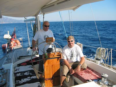 "Jamie & Liz agreed it was time to break out of the ""Black Hole"" and actually sail in to the Mediterranean. Within Marmaris bay katabatic winds and unpredictable breezes make sailing challenging. We entered the Sark Bogazi straight, which proved to be much wider than it appeared on the chart, and the winds picked up so we commenced tacking and making good progress. After about ¾ mile we broke out and started some serious stuff with 3 sails out, proving that with a ketch rig you don't need the mainsail if you want to cruise comfortably. Before long, however the Skipper decided it was time to turn right round a full 180 degrees and head due west towards Turunc, which is where we would be mooring up for the night. The wind was dropping before but now it was down to a whisper and then as we reached the wind shadow of the high hills facing us, we almost stopped. So it was on with the engine and aim for the beach.  Neither Jamie nor Liz had been here before so we all consulted Rod Heikel's book, which seemed optimistic about safe anchorage. Sure enough there were so many Turkish boats (especially the mini-gulets) that we abandoned the idea of tucking ourselves right in but took the more prudent option of anchoring just in front of the bathing area.  Swimming in Turunc Source: M&L Furlong  We had just got our swimming togs on when a Turkish boat stuffed full of English tourists came right up behind us and dropped anchor- obviously we were in his favourite spot! Fortunately, they did not stay too long and eventually left us in peace, except yet again an ice cream man came by yelling out his wares. After that, we were able to swim and snorkel in crystal clear water before watching the sun go down as we sipped our aperitifs on deck.  Then it was the dreaded wobbly blancmange ride to the village quay where a ""kind local"" helped us ashore. Turunc is a small resort with a funicular railway (no doubt because it's on a mountainside). Although it gives the impression of being quite remote, it's actually touristy but not too bad. After a browse amongst the tourist tat in the shops, looking for a bracelet for our granddaughter Jamie & Liz spied a bar for a top up and promptly sat down, whilst we headed for the nearest cash machine! In ordering drinks for us we are impressed with Jamie & Liz's improving Turkish vocabulary. We stuck to wine for our aperitif before we settled on an eatery. We ended up on the front looking out into the bay at the restaurant that the ""kind local"" manages, for an excellent meal with plenty of local red to wash it all down, but it's a cash only bill. Then back into the wobbly inflatable for a smooth ride out to Esper (with torch clutched tightly in hand). At this point Lesley opted for her bed, but Jamie suggested opening ""that bottle of red you brought from England"". Since Mike is so weak willed he said ""what a good idea"" when in fact he had already had too much. Whilst quaffing more wine and noticing that Esper had sprouted and extra 2 masts, something flashed past him in the dark and then zoomed back again behind him. It was Millyu showing off her prowess at lightning reactions and seeing in the dark-it's bit disconcerting until you get used to it. Well past midnight, Jamie said he was going to bed so Mike took the hint and staggered off feeling jaded."