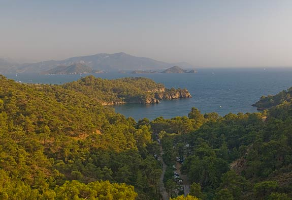 The late afternoon sun lights up the northern side of Fethiye Bay with Delikliadalar Island in the middle distance and Fethiye town in the background