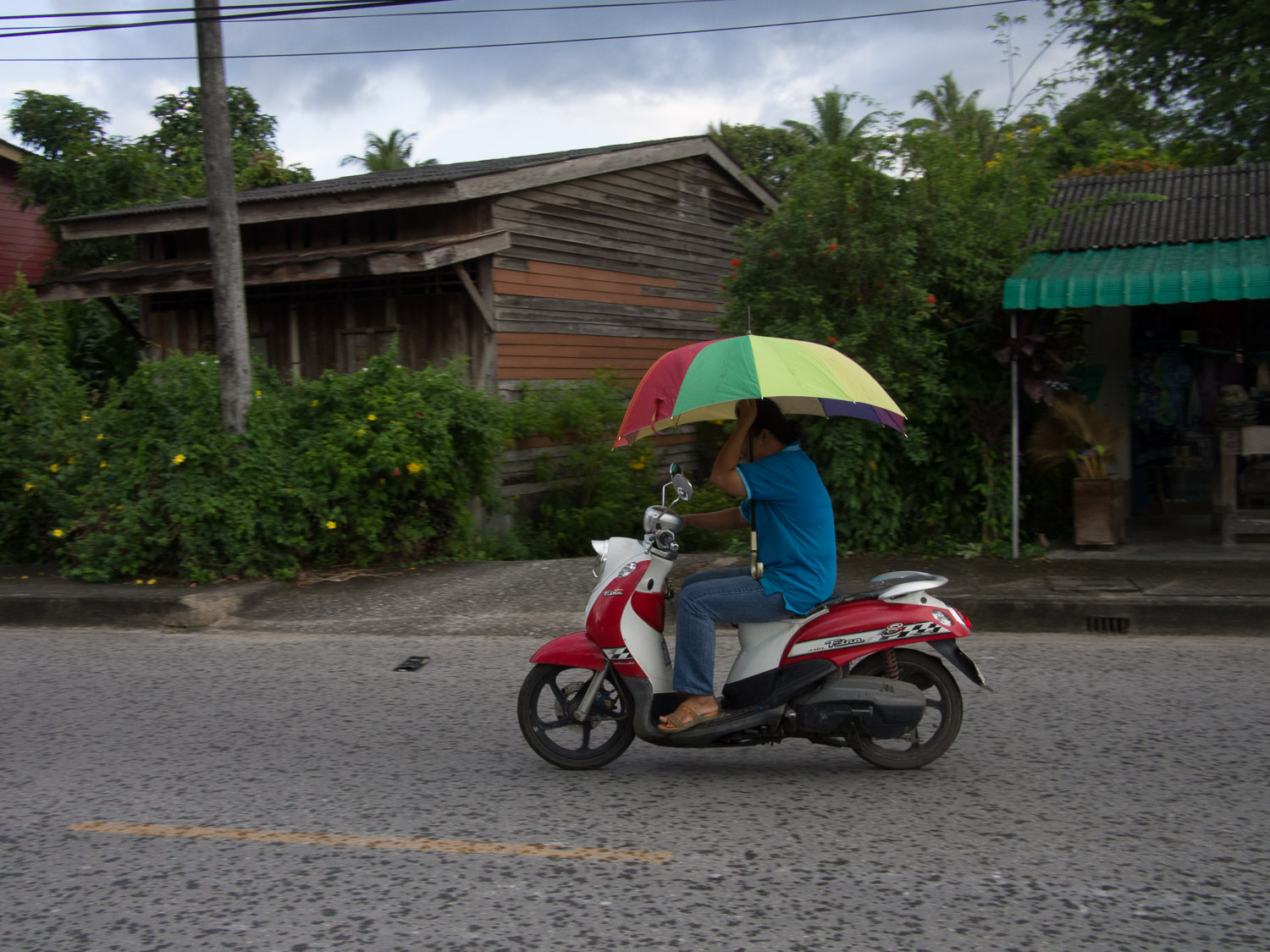 A motorcyclist shelters from the rain in Satun, Thailand