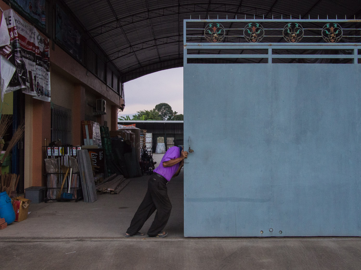 Opening a door to a warehouse in Satun, Thailand