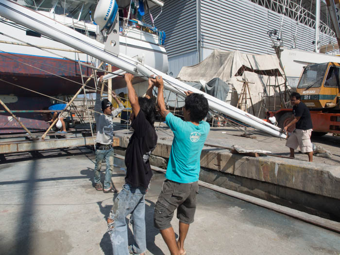 Lowering the mizzen mast and positioning it onto oil drums