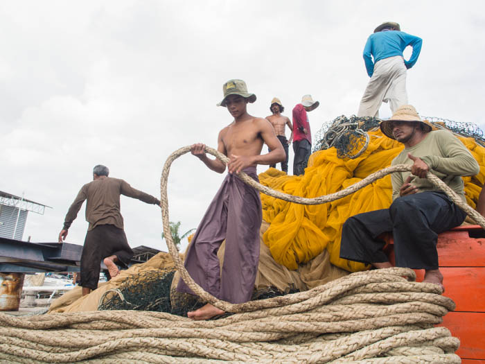 Local fishermen haul in their nets before lifting the boat