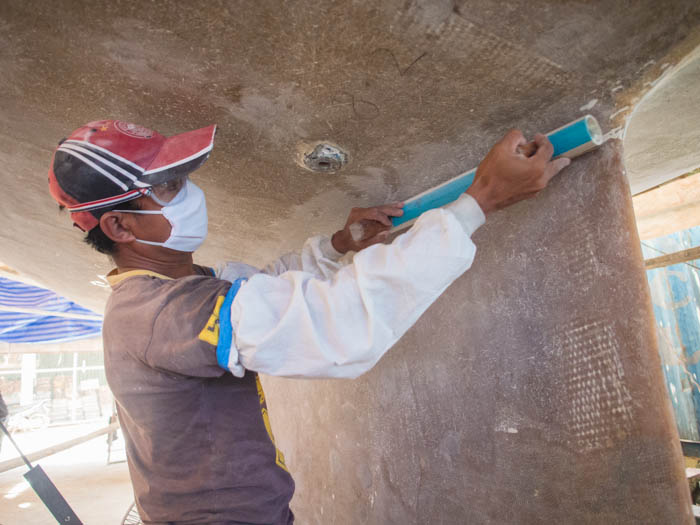 Yodchai uses a rounded faring sander to tackle the curvature of the keel
